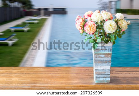 Flower vase on rustic tabletop over blurred modern swimming pool  background - stock photo