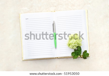 Flower with pen on an open note book. - stock photo