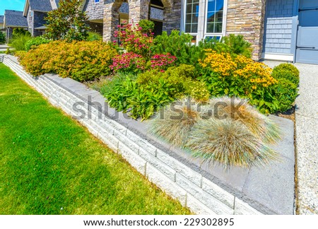 Flowerbed, flowers and stones in front of the house, front yard. Landscape design. - stock photo