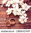 Flowering branch with white delicate flowers on wooden surface. Wedding rings. Wedding bouquet, background. Empty wooden tabletop  - stock photo