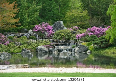 Flowering Japanese garden with pond and water cascades. - stock photo