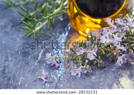 Flowering rosemary on blue slate, with bottle of olive oil and balsamic vinegar.  Shallow depth of field, with focus on rosemary flowers.