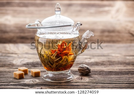 Flowering tea in glass teapot on rustic wooden background - stock photo