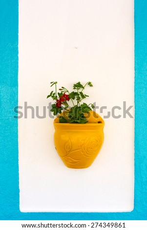 Flowerpots hanged on the  colorful walls and windows of the beautiful old houses in Bozcaada - stock photo
