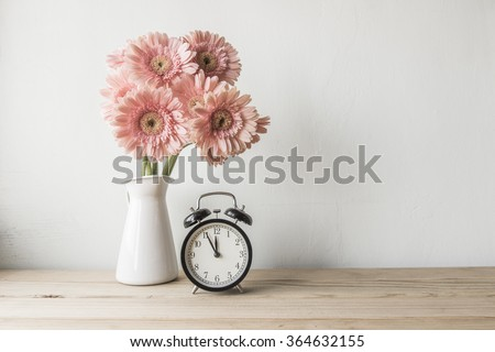 flowers and  alarm clock on a white wall shelf - stock photo