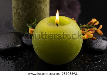 flowers and candle on black stones  - stock photo