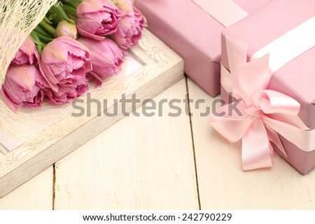 Flowers and gift box on wooden background with copy space - stock photo