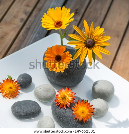 Flowers and stones on wooden background - stock photo
