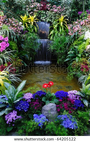 Flowers and waterfall in indoor garden, vancouver island, british columbia, canada - stock photo