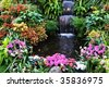 Flowers and waterfall inside the historic butchart gardens (over 100 years in bloom), vancouver island, british columbia, canada - stock photo