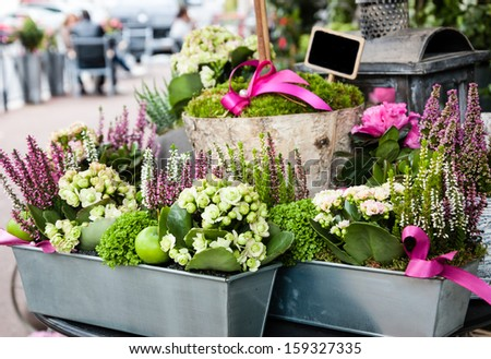 Flowers arrangement with green apples and pink bow in metal box at the entry to the flower shop in France. Cafe tables at background. - stock photo
