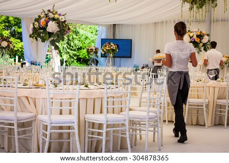 Flowers. Banquet hall in white, working waiters. Wedding. - stock photo