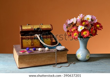 Flowers, books, jewelry box on the table - stock photo