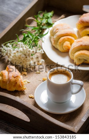 Flowers, croissant and coffee for breakfast - stock photo
