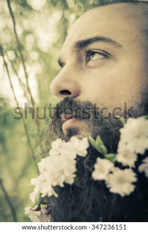 Flowers decorate the beard of this young man enjoying nature