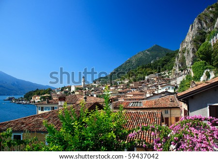 Flowers frame the rooftops of Limone on Lake Garda Italy - stock photo