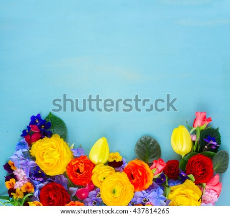 Flowers fresh festive border composition on blue wooden table background with copy space - stock photo