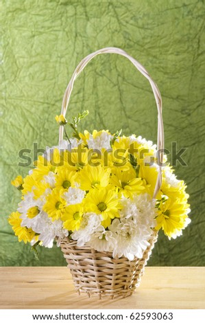 Flowers in a basket over  green textured background - stock photo