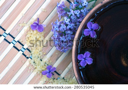 Flowers in a bowl color of brown with sea salt for SPA - stock photo