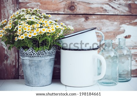 Flowers in a tin can, glass bottles and vintage enamel mugs on wooden background, cozy home rustic decor, cottage living - stock photo