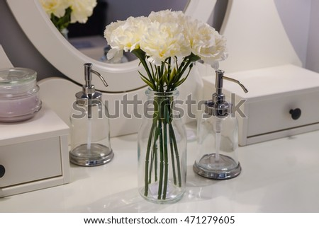 Flowers in a vase on the table in bathroom