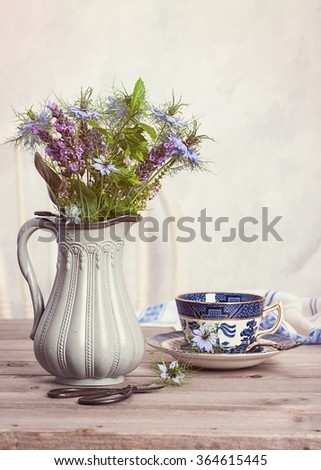 Flowers in antique jug with cup of tea - stock photo