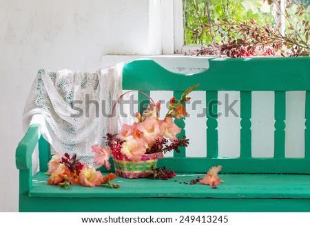 flowers in basket on bench indoor - stock photo