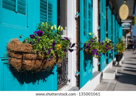 Flowers in baskets hang off shutter doors during Mardi Gras in New Orleans, Louisiana, USA - stock photo