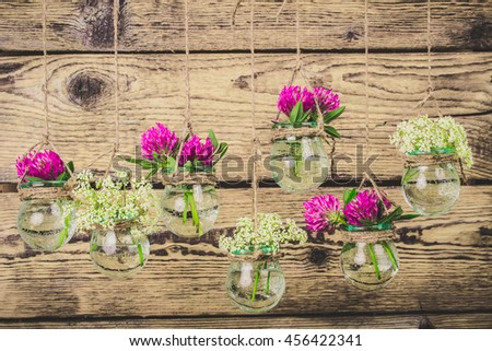 Flowers in jars on a string.