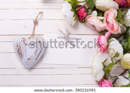 Flowers in pink colors with  decorative heart  and empty tag on white wooden background. Selective focus is on tag. Place for text.  - stock photo