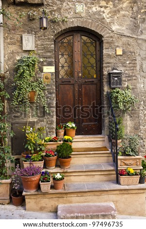 Flowers in pots on the stone steps medieval house in Assisi, Italy - stock photo