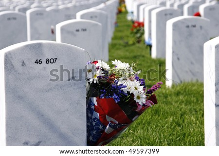Flowers memorialize the grave of a fallen soldier at the Fort Logan National Cemetery in Colorado, USA (shallow depth of field). - stock photo