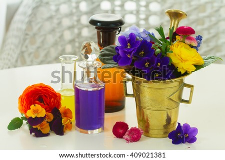 Flowers, mortar and bottles of potions, herbal medicine - stock photo