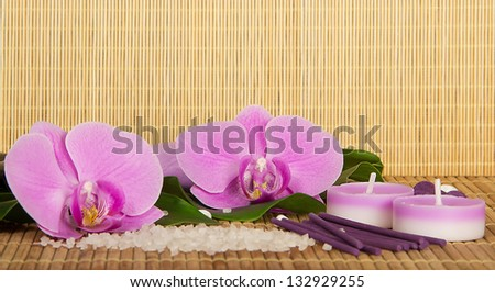 Flowers of an orchid and set for Spa on a bamboo cloth. Beige background - stock photo