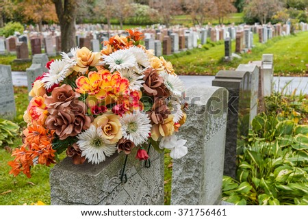 Flowers on a headstones in a cemetary (cemetery) with hundreds of tombstones in the background - stock photo