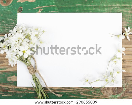 Flowers on vintage wooden planks with blank paper