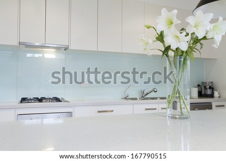 Flowers on white kitchen bench with splashback - stock photo