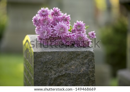 Flowers rest on headstone in cemetery - stock photo