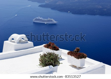 Flowers standing on the white roof. Blue sea and touristic ferry are on the background. Santorini. Greece. - stock photo