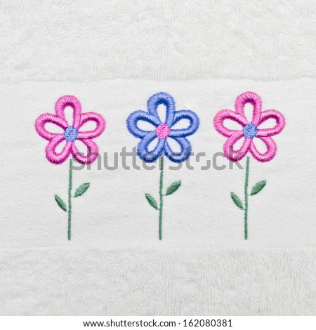 Flowers stitched into a white towle as a background image - stock photo