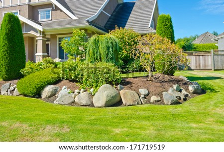 Flowers, stones and nicely trimmed bushes in front of the house, front yard. Landscape design. - stock photo