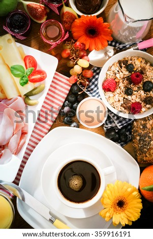 Flowers surrounding breakfast of coffee, cereal and cold cuts - stock photo