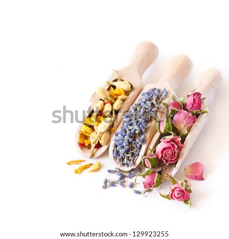 Flowers tea collection in a wooden scoops on a white background.