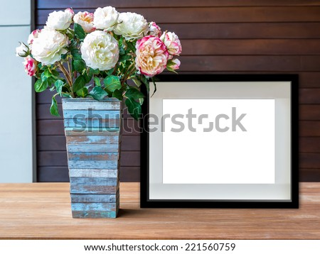 Flowers vase and blank black picture frame on wooden desktop - stock photo