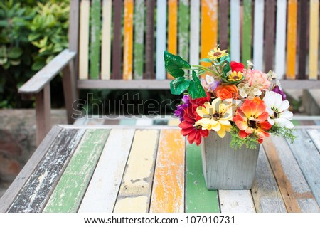 Flowers vase put on the old paint wood table