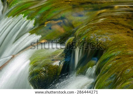 Flowing cascade of water over Moss covered stones in a shallow brook - stock photo
