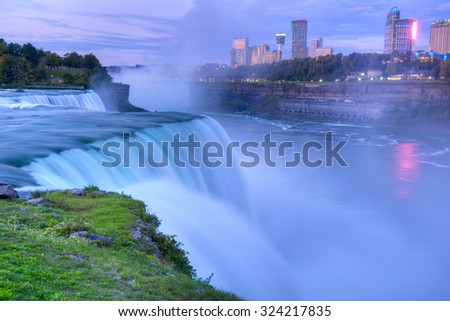 Flowing Niagara Falls from the American side with the skyline of the city of Niagara Falls in the background at dawn. The Niagara Falls is one of the largest and most famous waterfall in the world. - stock photo