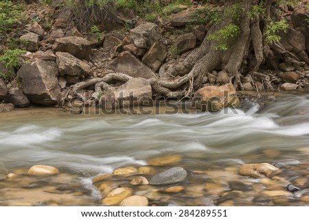 Flowing river across the river rocks - stock photo