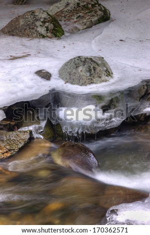 Flowing river in winter from the Myrtle Creek near Bonners Ferry, Idaho.