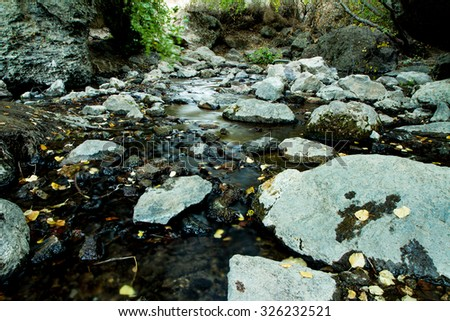 Flowing water against the rocks creating a little stream - stock photo
